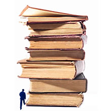 An image of a person who is dwarfed by a huge pile of books, several stories high